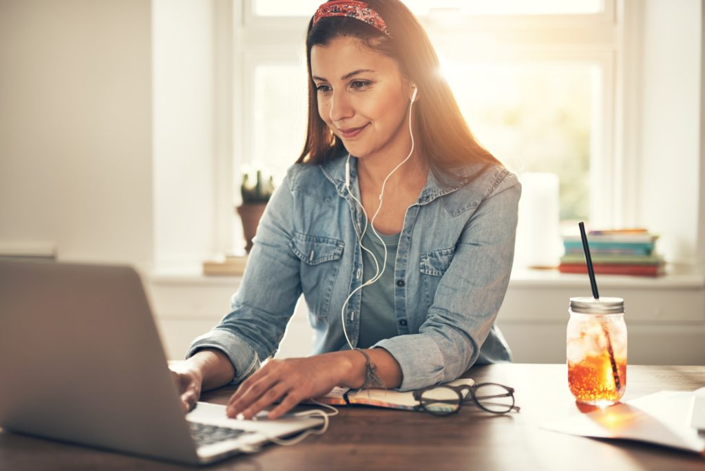 Smiling young businesswoman in headphones using laptop